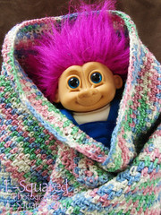 A smiling purple-haired troll doll wrapped up in a crocheted blanket made of variegated blue, green, pink and white yarn