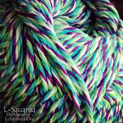 close up of yarn skein showing the twisted strand of white, lime green, cyan blue and grape purple