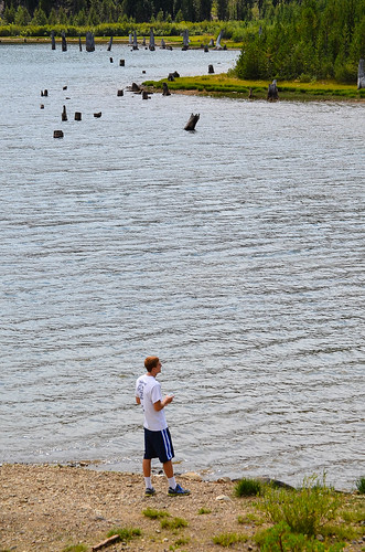 A young man at the edge of a river.