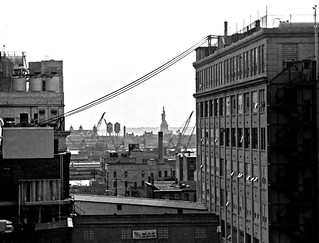 Daily life in the old Jersey City. Abandoned 19th century factories on the Morris Canal, crane graveyards, the Statue of Liberty and Ellis Island (itself closed and decrepit) from the roof of an empty warehouse near the Colgate plant. June 1975.