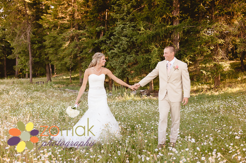 Romantic photo of bride and groom walking through forest and field of daisies.