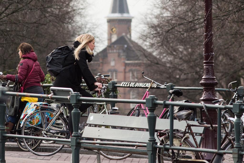 Красивая женщина на велосипеде в Амстердаме