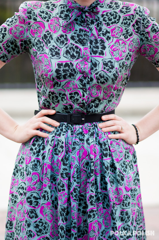 Abstract floral print 1940s dress in hot pink and black on a blue ground with a pussy bow neckline and self-covered buttons