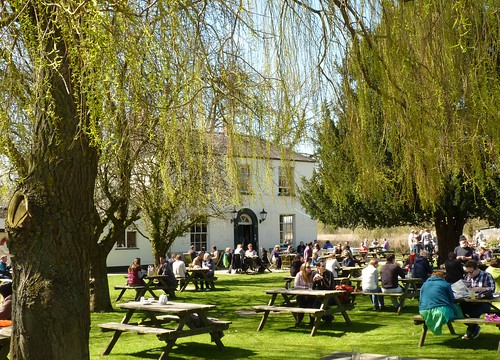 Beer garden full of people enjoying a drink in the sun at the Isis Farmhouse