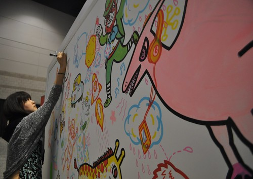 Artist You Byun Drawing Whimsical Critters during BlogHer 2013 in the Verizon Booth.