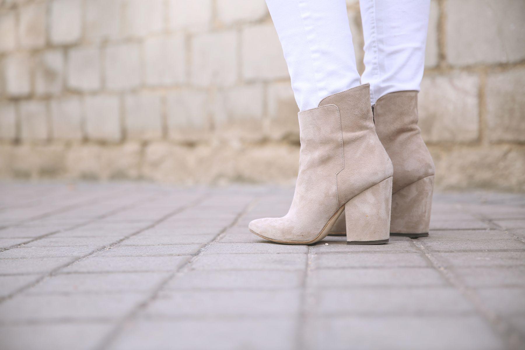 Casual look con abrigo de paño, vaqueros blancos, gorro de lana y botines nude