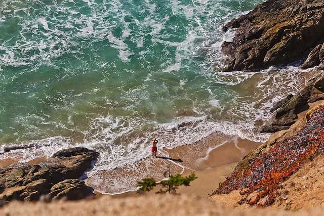 A man stands near the crashing waves of Grey Whale Cove Beach
