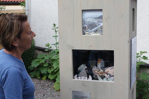 Barbro Mellqvist visar bilder och ett tittskåp.