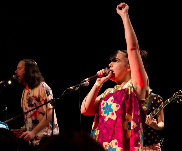 Kathleen Hanna, with her arm raised, singing at the front of her band