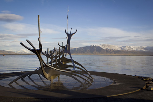 metal skeleton sculpture of a viking ship in front of water and mountain range