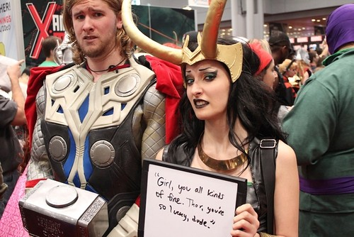 "A cosplayer team dressed up as Thor and Jane Foster hold a sign that says, ""Girl you all kinds of fine. Thor, you're a lucky dude."""