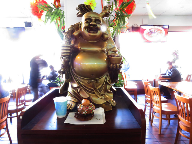 Buddha statue at Uncle Benny's Donuts with offerings / decorations for Chinese New Year 2015; The Sunset, San Francisco (2015)