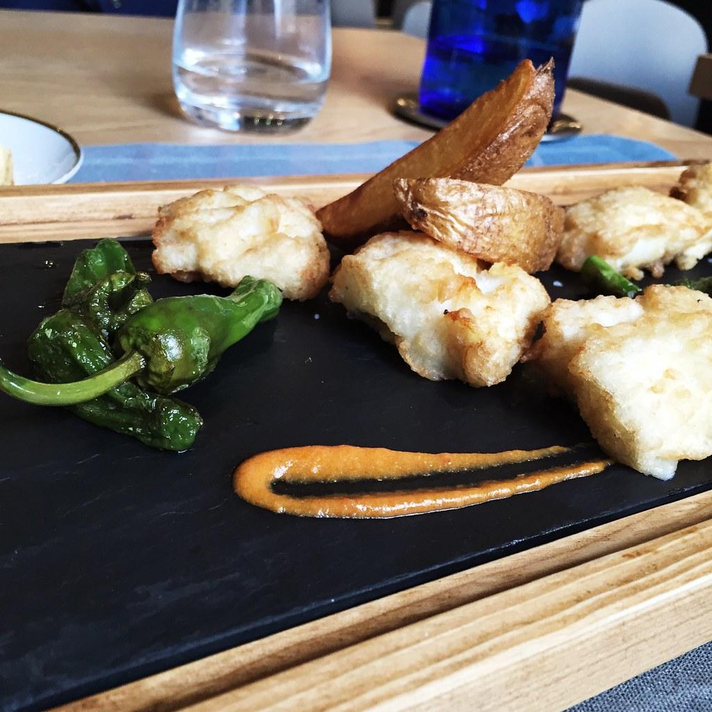 Merluza rebozada con verduritas, patata delixe y salsa romescu