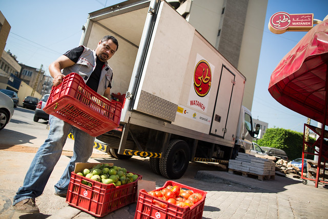 Fresh fruit and vegetables are delivered to a Wataneh grocery shop by a Wataneh delivery truck.