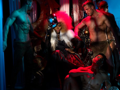 Ebony Bones, wearing a fancy top hat, surrounded by shirtless men