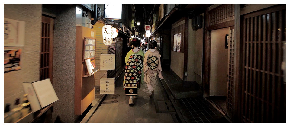 Two Maikos (Apprentice Geishas) Walking in Pontocho by Night, Kyoto – Japan