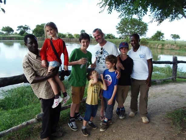 A family posing for a photo at the hippo pool in Mikumi National park during game drives