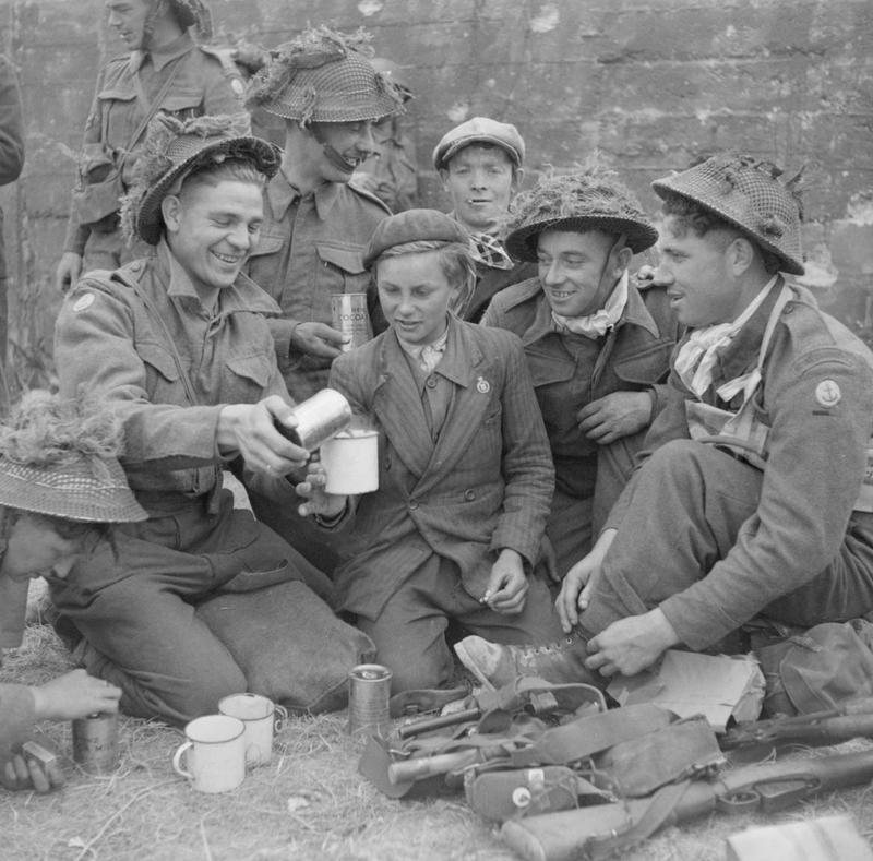 Royal Engineers serving with a 50th Division Beach Group share cocoa with a French boy in the village of Ver-sur-Mer