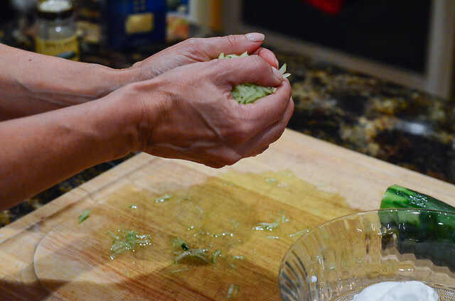 The shredded cucumber are being squeezed by hand and the liquid is dripping onto a cutting board below.