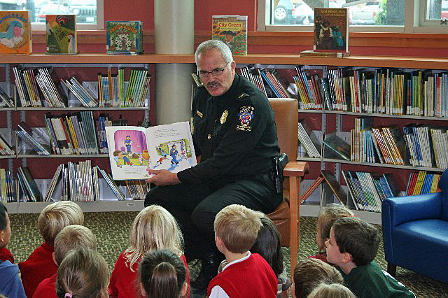Police Chief J. Thomas Manger reading to children