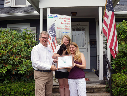 Thomas Williams, USDA Rural Development State Director for Pennsylvania presents a Certificate of Appreciation to Misty Allen, her daughter Deanna and their new puppy Odee for National Homeownership Month. Ms. Allen's new mortgage is less than she previously paid in rent.  (USDA Photo)