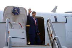 U.S. Secretary of State John waves goodbye at the airport in Lagos, Nigeria, after he met with Nigerian President Goodluck Jonathan and his re-election challenger, retired Major-General Muhammadu Buhari, on January 25, 2015, for conversations urging both candidates to accept the results of their upcoming general-election vote. [State Department Photo/Public Domain]