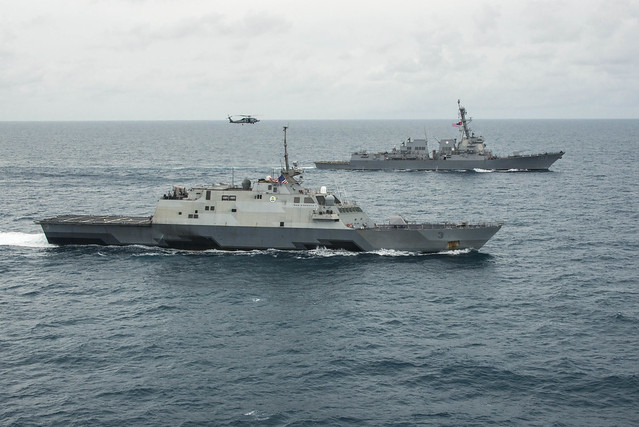 JAVA SEA - The littoral combat ship USS Fort Worth (LCS 3), bottom, the guided missile destroyer USS Sampson (DDG 102), and an MH-60R Seahawk from Helicopter Maritime Strike Squadron (HSM) 35 operate together in the Java Sea while supporting the Indonesian-led search effort for AirAsia flight QZ8501.