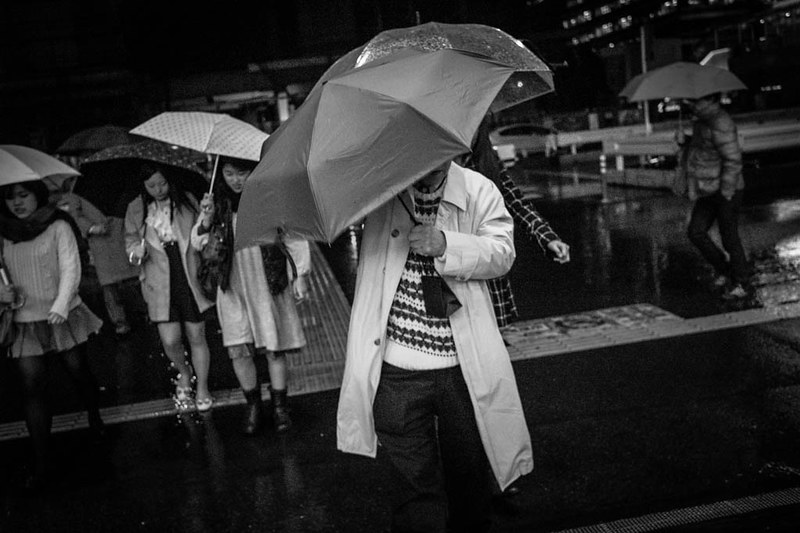 Man with umbrella at night in Shinjuku.