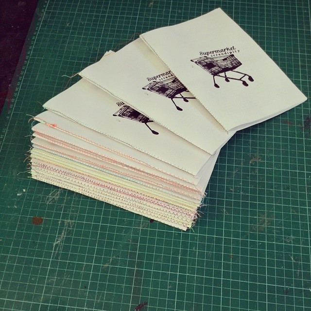 Messy, colourful binding on two dozen zines!