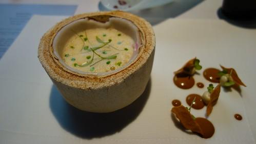 Caldo de leche de coco con berberechos, zamburiñas y pochas servido dentro de un coco joven