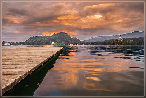 sunset lake reflection church water clouds pier europe slovenia bled