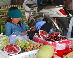 Fruit seller playing on iPhone