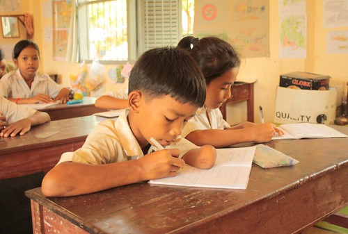 A boy with a physical disability is writing. Cambodia