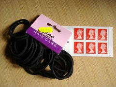 "A bunch of black hairbands held together by a pink-and-purple cardboard hang-tag with ""[...]ine LinesUK HAIR CARE"" printed on it and a yellow price sticker reading ""£1.19p"". Underneath this is an open book of six first-class stamps. These items are lying on a pale wood-effect table."