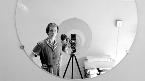 A self-portrait of Vivian Maier. She stares at the camera, which is pointed at a mirror reflecting the mirror and Vivian infinitum. A captivating photograph.