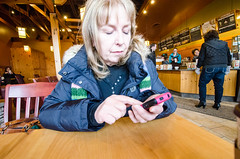 Mom using smartphone at Caribou Coffee