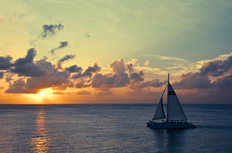 Cataraman sail through the sunset