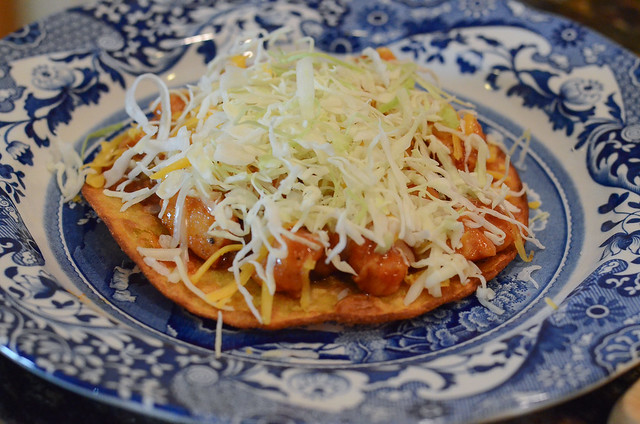 A crispy tortilla topped with chicken, BBQ sauce, cheese, and coleslaw.
