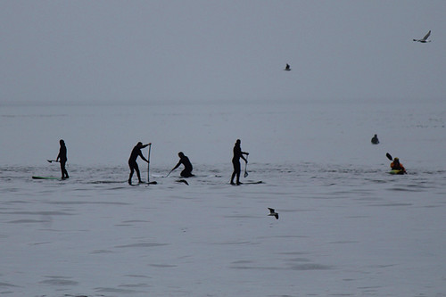 Paddlers, kayakers and surfers look like stickmen at Jordan River, Vancouver Island, British Columbia