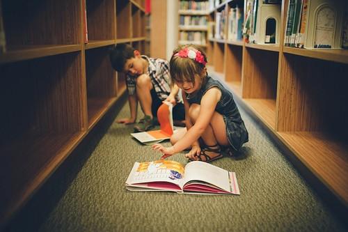 bimbo e bimba che sfogliano un libro colorato tra le scaffalature di una biblioteca