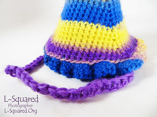 Close-up of the ruffle around the bottom edge of the  hat and the foundation-double crochet chin strap.