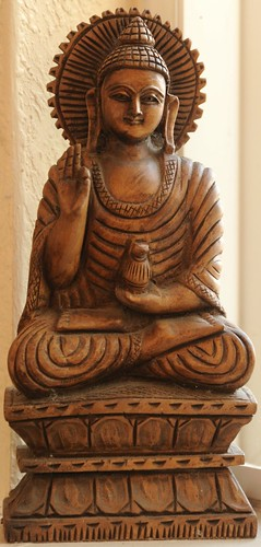Haloed Buddha statue in wood, holding his right hand in the perfection mudra, and a vase in the left, feet and legs in the lotus position, South Bay Vajrayana, Cupertino, Silicon Valley, California, USA by Wonderlane