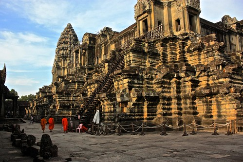 Monks walk around the central towers of Angkor Wat