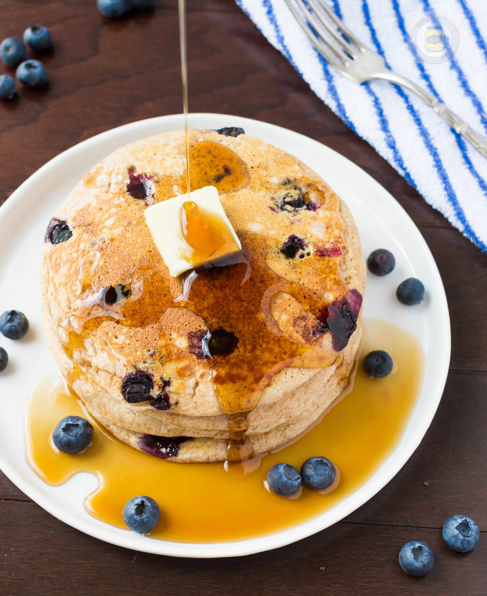 whole wheat buttermilk pancakes with blueberries on white plate with a pat of butter pouring pancake syrup on top