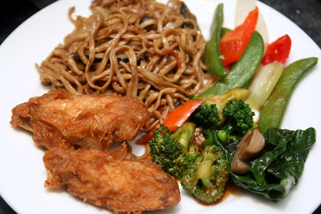 Platter of noodles, chicken wings and vegetables