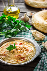 Hummus in metal bowl on  wooden table.