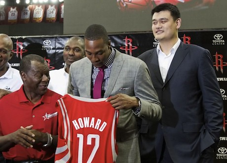 July 13, 2013 - Yao Ming stands behind Dwight Howard as he holds up his jersey.  Former Rocket Calvin Murphy looks on.