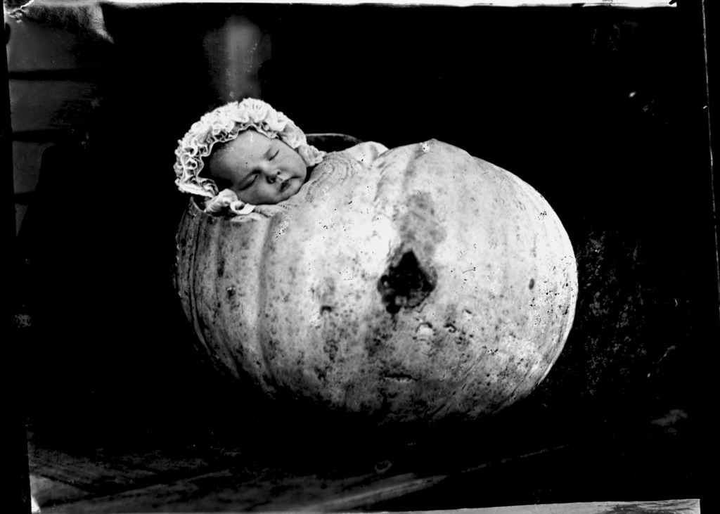 Unidentified baby lying in a hollowed out pumpkin : part of a mixed selection of lantern slides and negatives from John Flynn's teaching days in Gippsland, and early AIM [Australian Inland Mission] /