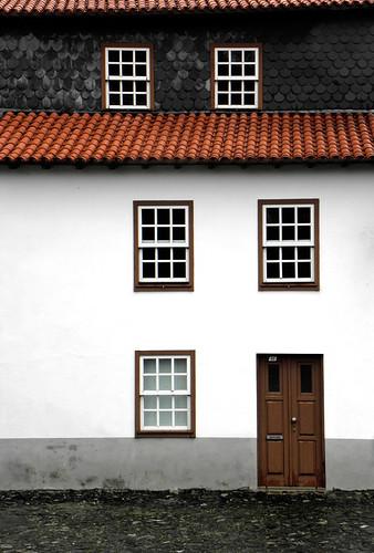 Geometrías en la fachada de una casa de Braganza. Juego de ventanas puerta y tejado.
