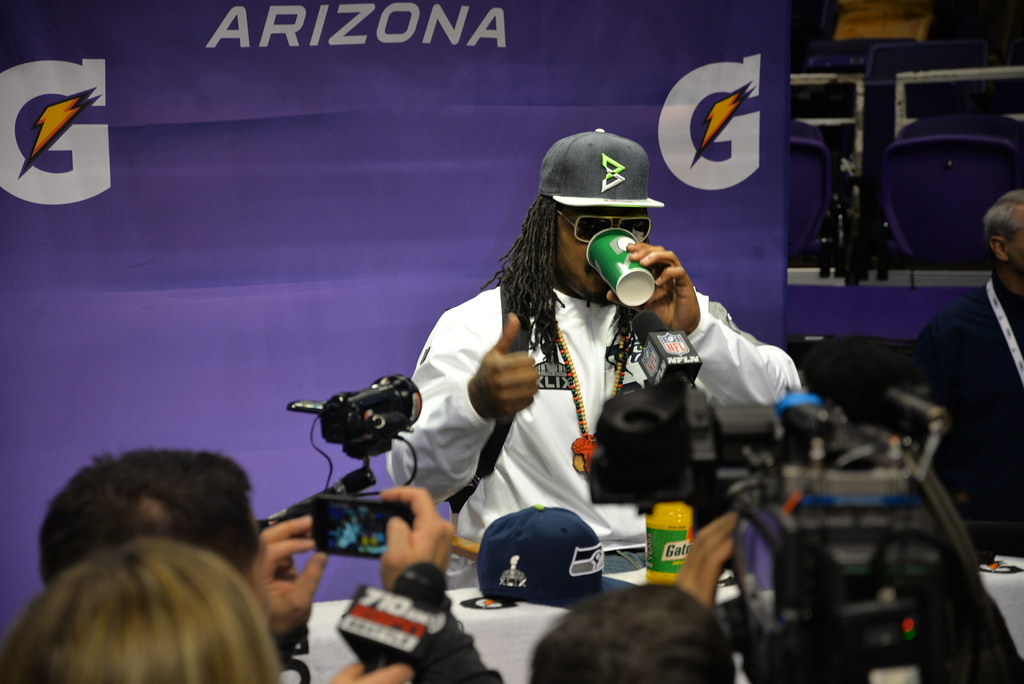 marchawn lynch wearing sunglasses at a press conference, giving a thumbs up